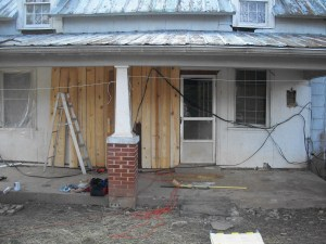 """front of old farmhouse gets new board and batten siding"""